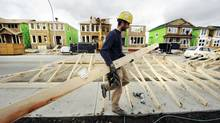A construction worker works on building new homes in Calgary, in this file photo. Canada's household saving rate eased to a near five-year low of 3.6 per cent in the fourth quarter of 2014, the third-straight quarterly decline, Statistics Canada said Tuesday as it released gross domestic product data. (TODD KOROL/REUTERS)