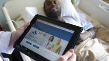 A doctor at Ottawa Hospital uses an iPad while seeing a patient in June, 2011. (ADRIAN WYLD/THE CANADIAN PRESS)