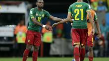 Cameroon's Henri Bedimo, left, and Joel Matip shake hands after losing 1-4 to Brazil at the group A World Cup soccer match between Cameroon and Brazil at the Estadio Nacional in Brasilia, Brazil, Monday, June 23. (Dolores Ochoa/AP)