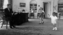 In this October 1962 file photo provided by the White House, President John F. Kennedy, left, claps time as his children Caroline, center, and John, Jr. dance in the Oval Office. (The Canadian Press)