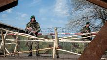 Ukrainian soldiers guard their tent camp near the village of Uspenka on April 18, 2014. (Evgeniy Maloletka/The Associated Press)
