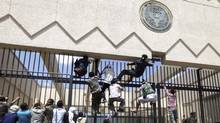 Protesters climb a fence at the U.S. embassy in Sanaa September 13, 2012. (MOHAMED AL-SAYAGHI/Reuters)