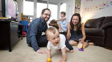 Andrew Geldard, his wife Dionne Hingston, daughter Mea, 3, and son Ethan, 1, play in their Junction-area apartment. (Kevin Van Paassen for The Globe and Mail)