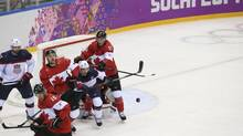 Canadian and U.S. players battle in front of the net for an airborne puck in their men's semifinal ice hockey game at the Bolshoy Ice Dome during the 2014 Winter Olympics in Sochi, Russia, Feb. 21, 2014. The Canadian team was victorious, winning 1-0, and faces Sweden in the gold medal game. (JOSH HANER/NYT)