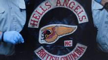 A Hells Angel vest being held by RCMP officers. (Handout/ The Globe and Mail/Handout/ The Globe and Mail)