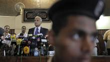 Judge Ahmed Rifaat, center-left, who will try Egypt's ousted leader Hosni Mubarak, speaks to the media as an Egyptian policeman stands guard in the foreground, at a press conference held at the High Court in downtown Cairo, July 31, 2011. (Nasser Nasser/AP/Nasser Nasser/AP)
