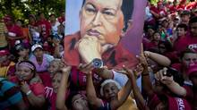 Supporters of Venezuela's President Hugo Chavez hold up an image of him during a campaign caravan from Barinas to Caracas, in Sabaneta, Venezuela, Monday, Oct. 1, 2012. (Rodrigo Abd/AP)