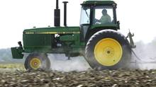 In this April 2, 2012 file photo, Derek Long uses a John Deere tractor to disk and cultivate a field in preparation for planting corn in Loami, Ill. (Seth Perlman/AP)