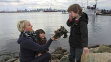 Elissa Wolfe shows her son, Caden, and niece, Sora, a seaweed-covered rock in North Vancouver. Increased radiation levels have been found in B.C. seaweed. (Jeff Vinnick/The Globe and Mail)