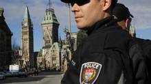 Ottawa police officers, with Parliament Hill in the background, guard the area around the National War Memorial in downtown Ottawa in this October 23, 2014 file photo. A review Ottawa undertook in the aftermath of the October attacks on Canadian soldiers, when a gunman also stormed Parliament, flagged gaps in the tools available to fight extremists. (BLAIR GABLE/REUTERS)