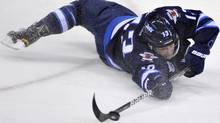 Winnipeg Jets' Kyle Wellwood makes a pass while falling to the ice against the Colorado Avalanche during the third period of their NHL hockey game in Winnipeg February 19, 2012. REUTERS/Fred Greenslade (FRED GREENSLADE)