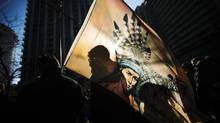 "First Nations protesters are silhouetted against a flag as the take in a ""Idle No More"" demonstration in Toronto, January 16, 2013. (MARK BLINCH/REUTERS)"