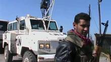 An armed member of the Al Yarmouk Martyr brigade is seen in front of a white vehicle with 'UN' written on it at what said to be Jamla, Syria near Golan Heights on March 6, 2013 in this still image taken from video posted on a social media website. Syrian rebels have seized a convoy of U.N. peacekeepers near the Golan Heights and say they will hold them captive until President Bashar al-Assad's forces pull back from a rebel-held village which has seen heavy recent fighting. The capture was announced in rebel videos posted on the Internet and confirmed on Wednesday by the United Nations in New York, which said about 20 peacekeepers had been detained. (REUTERS TV/Reuters)
