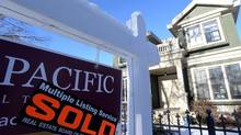 A real estate sold sign is shown outside a house in Vancouver, Tuesday, Jan.3, 2017. Victoria home prices have surged, and the driving force behind the hot market has a familiar ring – offshore buyers. (Jonathan Hayward/THE CANADIAN PRESS)