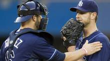 Tampa Bay Rays catcher Chris Gimenez gives pitcher Jeff Niemann a pat on the shoulder after he was hit by a grounder by Toronto Blue Jays Adam Lind during first inning AL action in Toronto on Monday May 14, 2012. THE CANADIAN PRESS/Frank Gunn (Frank Gunn/CP)