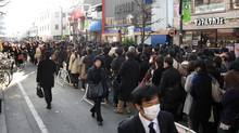 """Commuters queue for a train at the Akihabara JR station in downtown Tokyo as only minimal service is maintained, on March 14, 2011. With ports, airports, highways and manufacturing plants shut down after the March 11 monster earthquake, the Japanese government predicted """"considerable impact on a wide range of our country's economic activities"""". (Jiji Press/AFP/Getty Images/Jiji Press/AFP/Getty Images)"""