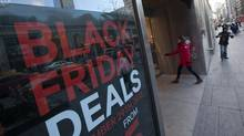 Shoppers walk past a Black Friday sale sign hanging in the window of H&M clothing store on Bloor Street in Toronto on November 27, 2013. (Deborah Baic/The Globe and Mail)