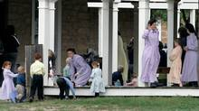 Adults and children, members of the Fundamentalist Church of Jesus Christ of Latter Day Saints, gather beneath a covered porch at one of the structures at their temporary housing, Fort Concho National Historic Landmark, in San Angelo, Texas, Wednesday, April 9, 2008. (Tony Gutierrez/ The Associated Press/Tony Gutierrez/ The Associated Press)