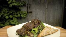 Toasty anchovy bread serves as a delicious accompaniment to skewered grilled steak and oyster-mushroom salad. (Peter Power/The Globe and Mail)