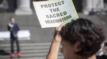 The First Nations community and the mining company are in a standoff over Fortune Minerals's plans to build an open-pit coal mine in the Sacred Headwaters of Northern British Columbia. Pictured, a woman holds a sign at a solidarity gathering in Vancouver. (John Lehmann/The Globe and Mail)