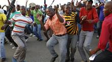 Striking miners dance and cheer after they were informed of a 22 per cent wage increase offer outside Lonmin's Marikana mine, 100 km northwest of Johannesburg, Sept. 18, 2012. (SIPHIWE SIBEKO/REUTERS)