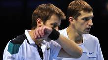 Max Mirnyi of Belarus (R) and his partner Daniel Nestor of Canada (L) talk between points against Nenad Zimonjic of Serbia and his partner Michael Llodra of France during their group B doubles match in the round robin stage on day five of the ATP World Tour Finals tennis tournament in London on November 24, 2011. AFP PHOTO / GLYN KIRK (GLYN KIRK/Getty Images)