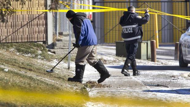 An investigator uses a metal detector and later sifts through collected debris from a lawn at the scene on a street in Brampton, Ont., on Jan. 24, 2013 where a 9-year old boy was shot late Wednesday evening, and later died of his injuries. (Peter Power/The Globe and Mail)