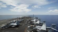 "A general view of the aircraft on the flight deck during a tour of the USS Nimitz aircraft carrier on patrol in the South China Sea in this file photo from May 23, 2013. The Nimitz and four other ships in its strike group moved into the Red Sea early September 1, 2013, U.S. defense officials said, describing the move as ""prudent planning"" in case the ships are needed for military action against Syria. (EDGAR SU/REUTERS)"
