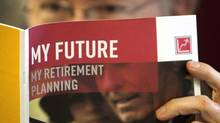 A man looks over a brochures offering various retirement savings options. (Ryan Remiorz/THE CANADIAN PRESS)