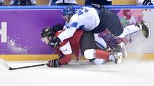 Finland's Juhamatti Aaltonen (top) takes down Canada's Jonathan Toews during second period preliminary round hockey action at the 2014 Sochi Winter Olympics in Sochi, Russia on Sunday, February 16, 2014. (Nathan Denette/THE CANADIAN PRESS)