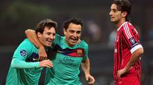 Barcelona's Argentinian forward Lionel Messi, left, and teammate midfielder Xavi Hernandez celebrate in front of AC Milan's midfielder Alberto Aquilani. (GIUSEPPE CACACE/AFP/Getty Images)