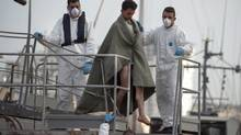 In this Saturday, Oct. 12, 2013 file photo, a man, covered in a blanket, is helped to disembark as he arrives at the Valletta harbor, Malta after a Maltese brought 143 survivors from a capsized smugglers' boat, most of the migrants in the latest tragedy were fleeing civil war in Syria. A sharp rise in the number of Syrians attempting the perilous sea voyage over the past three months highlights the crushing life-and-death decisions facing many who fled to Egypt to escape Syria's armed conflict, according to rights group Amnesty International. (Lino Arrigo Azzopardi/AP)