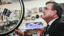 Finance Minister Jim Flaherty takes time out to look over a bicycle after a news conference at Joe Mamma's bicycle shop in Ottawa, in this October 18, 2012 photo. The owner of the shop where Flaherty last year trumpeted the benefits of his budget, says he feels misled. (FRED CHARTRAND/THE CANADIAN PRESS)