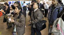 People look at the information board at the The National Job Fair & Training Expo at the Metro Toronto Convention Centre, 2012. (J.P. MOCZULSKI For The Globe and Mail)