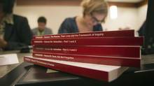 A reporter reads through the Missing Women's Commission of Inquiry, shortly after it was made public in Vancouver on Dec. 17, 2012. (Ben Nelms/Reuters)