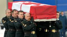 Honor guards carry the casket of Sergeant George Miok to a waiting hearse at Canadian Forces Base Trenton, Ontario January 3, 2010. Sergeant Miok's body arrived home to Canada with three other Canadian soldiers and journalist Michelle Lang. All five died when an improvised explosive device detonated near their armored vehicle south of Kandahar City, Afghanistan December 30 2009. (FRED THORNHILL/Fred Thornhill /Reuters)
