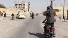 A man holds up a knife as he rides on the back of a motorcycle touring the streets of Tabqa city with others in celebration after Islamic State militants took over Tabqa air base, in nearby Raqqa city August 24, 2014. (STRINGER/REUTERS)