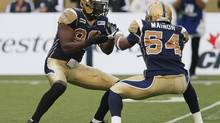 Winnipeg Blue Bombers' Alex Hall (96) and Kenny Mainor (54) celebrate Hall's sack on Montreal Alouettes' Anthony Calvillo during the first half of their CFL game in Winnipeg, Friday, Aug.3, 2012. (John Woods/THE CANADIAN PRESS)