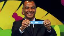 "Former Brazil soccer player Cafu holds the slip showing ""Brazil"" during the draw for the 2014 World Cup (Reuters)"