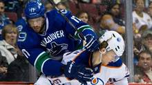 Vancouver Canucks' Ryan Kesler, left, and Edmonton Oilers' Philip Larsen, of Denmark, collide during first period NHL hockey action in Vancouver, B.C., on Friday December 13, 2013. (DARRYL DYCK/THE CANADIAN PRESS)