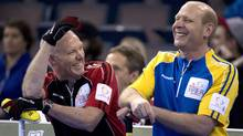Ontario skip Glenn Howard, left, shares a laugh with Alberta skip Kevin Martin during the evening draw at the Tim Hortons Brier in Edmonton, Alta. Friday, March 8, 2013. (The Canadian Press)