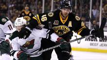 Boston Bruins centre David Krejci holds back Minnesota Wild center Mikael Granlund as they chase the puck during the second period of an NHL hockey game, Monday, March 17, 2014, in Boston. (Associated Press)