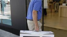 An Apple customer enters an Apple store in Palo Alto, Calif. (Paul Sakuma/AP)