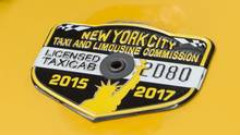 In this June 26, 2017 photo, the medallion of taxi driver and taxi medallion owner Marcelino Hervias is affixed to the hood of his taxicab on New York's Upper West Side. Three credit unions that specialized in loaning money against cab medallions, the hard-to-get licenses that allow traditional taxis to operate, have been placed into conservatorship as the value of those medallions has plummeted. (Richard Drew/AP)