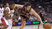 Raptors guard Kyle Lowry, left, battles for the ball against Chicago Bulls guard Marco Belinelli during first-half NBA action at the Air Canada Centre in Toronto on Wednesday. Lowry had 26 points in the loss. (Nathan Denette/THE CANADIAN PRESS)