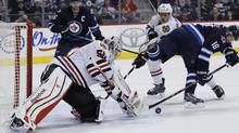 Chicago Blackhawks goaltender Corey Crawford (50) stops Winnipeg Jets' Bryan Little (18) backhander as Hawks' Niklas Hjalmarsson (4) and Jets' Andrew Ladd (16) look for the rebound during second period NHL action in Winnipeg on Thursday, November 21, 2013. (JOHN WOODS/THE CANADIAN PRESS)