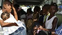 Children suspected of being involved in an illicit adoption scheme sit in a local police car in Port-au-Prince January 30, 2010. Haitian police have arrested 10 U.S. citizens caught trying to take 33 children out of the earthquake-stricken country in a suspected illicit adoption scheme, authorities said on Saturday. (Guy Delva/Reuters) (STR)
