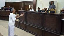 In this Saturday, May 3, 2014 file photo, Canadian-Egyptian acting Al-Jazeera bureau chief Mohammed Fahmy talks to the judge in a courthouse near Tora prison along with several other defendants during their trial on terror charges in Cairo, Egypt. On Sunday, Feb. 8, 2015, court officials said the retrial of two detained Al-Jazeera English journalists will begin on Feb. 12 in a case widely dismissed by rights groups as a sham. Their colleague Peter Greste was released earlier this month and deported to Australia. (Hamada Elrasam/The Associated Press)