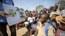 A man shows a picture chart regarding the Ebola virus to students during a United Nations Children's Fund (UNICEF) Ebola awareness drive in Toulepleu, at the border of Liberia, western Ivory Coast, November 4, 2014. (THIERRY GOUEGNON/REUTERS)