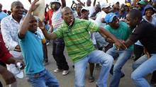 Striking miners dance and cheer outside Lonmin's Marikana mine Sept. 18, 2012 after being informed of a 22-per-cent wage increase offer. (SIPHIWE SIBEKO/REUTERS)